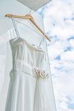 在轻的墙壁前面的白色婚礼礼服  免版税库存照片
