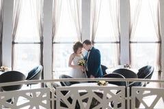 在他们的婚礼庆祝的迷人的新娘和新郎拥抱前额在豪华餐馆 免版税库存照片