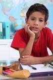 在他的学校书桌上的男孩 免版税库存图片
