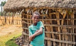 在他的家前面的埃赛俄比亚的年轻男孩 库存图片