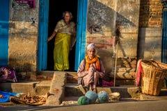 在他们的家前面的老夫妇在加德满都,尼泊尔 免版税库存图片