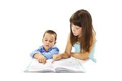 在他们的家庭作业的两个逗人喜爱的孩子画象  库存图片