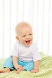 在他的小儿床的婴孩笑 库存照片
