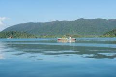 在水的小木小船有山背景 免版税图库摄影