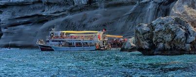 在水的小船在岩石岸附近 免版税库存照片