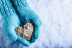 在轻的小野鸭的女性手编织了有纠缠的米黄亚麻心脏的手套在白色雪背景 St情人节概念 库存图片