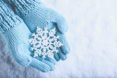 在轻的小野鸭的女性手编织了有闪耀的美妙的雪花的手套在雪背景 冬天和圣诞节概念 免版税库存照片