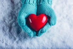 在轻的小野鸭被编织的手套的妇女手在雪背景中拿着美好的光滑的红色心脏 St华伦泰概念 免版税库存照片