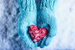 在轻的小野鸭被编织的手套的妇女手拿着在雪的美好的纠缠的葡萄酒红色心脏 St华伦泰概念 免版税库存图片