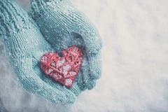 在轻的小野鸭被编织的手套的妇女手拿着在雪背景的美好的光滑的红色心脏 爱,圣华伦泰概念 免版税库存图片