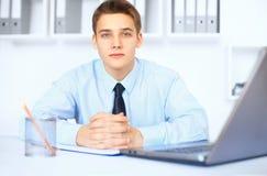 在他的工作场所的年轻微笑的商人在办公室 免版税库存图片
