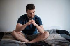 在他的床上安装的沮丧的人 免版税库存图片
