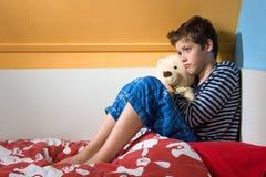 在他的床上的哀伤和沮丧的男孩 库存图片