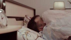 在他的床上被吓唬和慢慢地拉扯在他自己的年轻人毯子 影视素材