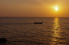 在水的惊人的热带橙色日落,与岩石剪影和一条小船在普吉岛海岛上,泰国 免版税库存图片