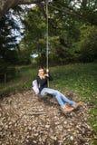 在绳索的愉快的少妇摇摆 免版税库存图片
