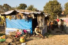 在他们的房子附近的未认出的可怜的人贫民窟的在Tripureshwor区,加德满都 免版税库存图片