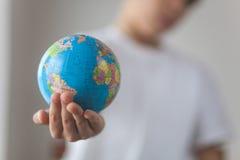 在他的手上举行玩具globus 免版税库存图片