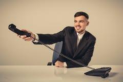 在他的手上的可爱的商人画象拿着电话 免版税库存照片
