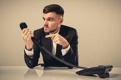 在他的手上的可爱的商人画象拿着电话 库存图片