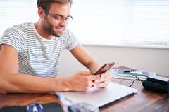 在他的手机的有吸引力的男学生繁忙的传讯在书桌 免版税库存图片