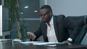 在他的智能手机和短信的答复的美国黑人的商人读书电子邮件 影视素材