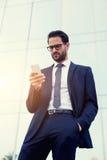 在他的智能手机的英俊的商人读书正文消息 免版税库存图片