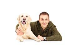 在他的最好的朋友拉布拉多狗旁边的一个年轻微笑的人 免版税图库摄影