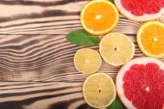 在轻的木背景的五颜六色和新鲜的柑橘 切成了两半桔子、柠檬和葡萄柚顶视图 复制空间 库存图片