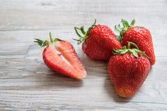 在轻的木背景的草莓 库存图片