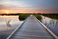 在水的木自行车道路在日落 免版税库存图片