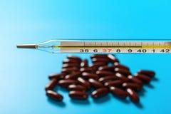 在40的水银温度表摄氏度与在背景的十二胶囊 免版税库存照片