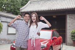 在他们的汽车前面的年轻夫妇 库存图片