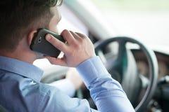在他的汽车的年轻商人在轮子谈话在流动酸碱度 库存照片