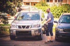 在他的汽车附近的愉快的人 免版税库存照片