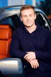 在他的汽车附近的愉快的英俊的人 免版税库存照片