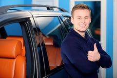 在他的汽车附近的愉快的英俊的人 库存照片