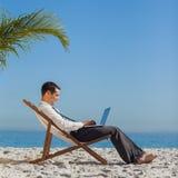 在他的海滩睡椅的年轻商人使用他的膝上型计算机 免版税图库摄影
