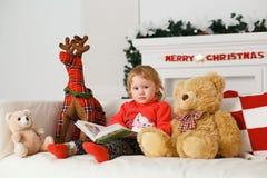 读在他的玩具圣诞节装饰的小女孩一本书 免版税库存照片