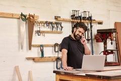 在他的电话的木匠业小企业主有膝上型计算机的 库存照片