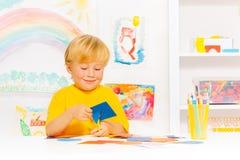 在类的白肤金发的小男孩切口纸板形状 免版税库存图片