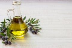 在轻的白色背景的橄榄油瓶 图库摄影