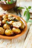在他们的皮肤和大蒜的被烘烤的嫩土豆土豆 库存图片