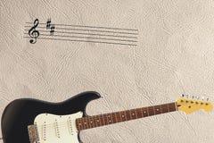 在轻的皮肤背景底部的梯级和固体经典电吉他  库存图片