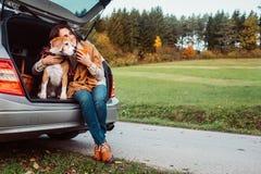 在他们的秋天自动旅行期间,有她的狗的妇女有茶时间 免版税库存照片