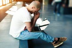 在他的笔记本的男性自由职业者工作在看起来现代的办公室空间沉思和担心,当考虑计划时 图库摄影
