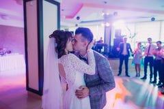 在他们的第一个舞蹈期间的亲吻的新婚佳偶在餐馆 免版税库存图片
