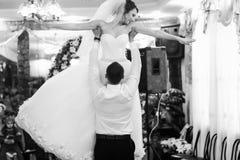在他们的第一个舞蹈期间,未婚夫在他的手上拿着新娘 库存照片