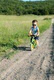 在他的第一辆自行车的男婴骑马没有脚蹬 免版税库存图片