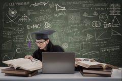 在类的繁忙的女性毕业生阅读书 免版税库存照片